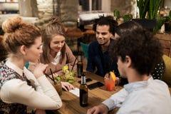 Amis heureux avec des boissons et facture à la barre ou au café Photographie stock