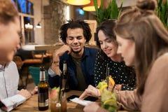 Amis heureux avec des boissons et facture à la barre ou au café Images stock