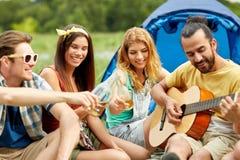 Amis heureux avec des boissons et guitare au camping Photographie stock