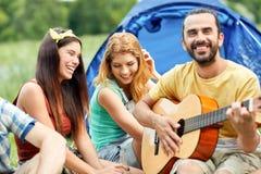 Amis heureux avec des boissons et guitare au camping Image libre de droits