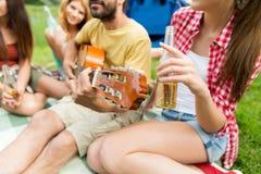 Amis heureux avec des boissons et guitare au camping Photos stock