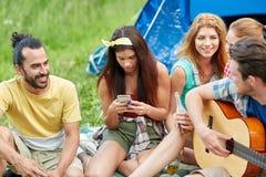 Amis heureux avec des boissons et guitare au camping Image stock