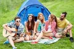 Amis heureux avec des boissons et guitare au camping Photos libres de droits