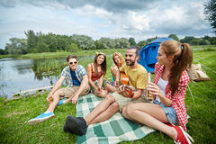 Amis heureux avec des boissons et guitare au camping Photographie stock libre de droits