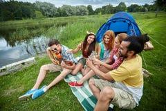 Amis heureux avec des boissons et guitare au camping Photo libre de droits