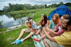 Amis heureux avec des boissons et guitare au camping Images stock
