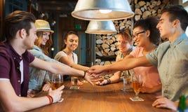 Amis heureux avec des boissons et mains sur le dessus à la barre Photos libres de droits
