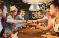 Amis heureux avec des boissons et mains sur le dessus à la barre Photographie stock libre de droits