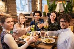 Amis heureux avec des boissons et nourriture au restaurant Photographie stock libre de droits