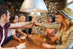 Amis heureux avec des boissons faisant la haute cinq à la barre Photo stock