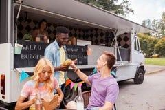 Amis heureux avec des boissons mangeant au camion de nourriture Photo stock