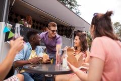 Amis heureux avec des boissons mangeant au camion de nourriture Photos stock