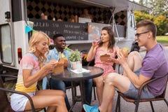 Amis heureux avec des boissons mangeant au camion de nourriture Image libre de droits