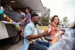 Amis heureux avec des boissons mangeant au camion de nourriture Photo libre de droits
