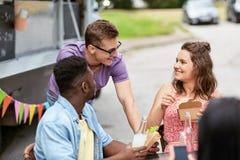 Amis heureux avec des boissons mangeant au camion de nourriture Images stock