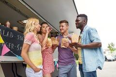 Amis heureux avec des boissons mangeant au camion de nourriture Image stock