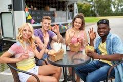 Amis heureux avec des boissons mangeant au camion de nourriture Photographie stock libre de droits