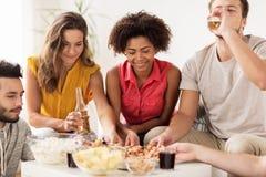 Amis heureux avec des boissons mangeant de la pizza à la maison Photo stock