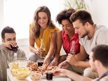 Amis heureux avec des boissons mangeant de la pizza à la maison Photo libre de droits