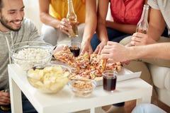 Amis heureux avec des boissons mangeant de la pizza à la maison Images libres de droits