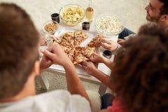 Amis heureux avec des boissons mangeant de la pizza à la maison Images stock
