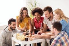 Amis heureux avec des boissons mangeant de la pizza à la maison Photographie stock libre de droits