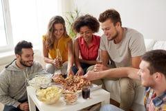 Amis heureux avec des boissons mangeant de la pizza à la maison Photos stock