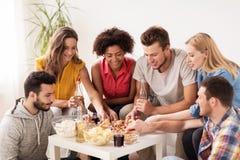 Amis heureux avec des boissons mangeant de la pizza à la maison Image libre de droits