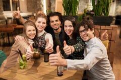 Amis heureux avec des boissons montrant des pouces à la barre Photo stock