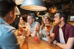 Amis heureux avec des boissons parlant à la barre ou au bar Photos libres de droits