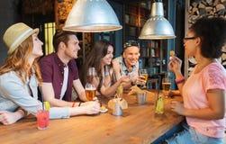 Amis heureux avec des boissons parlant à la barre ou au bar Image libre de droits