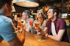 Amis heureux avec des boissons parlant à la barre ou au bar Images stock
