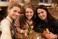 Amis heureux avec des boissons prenant le selfie au café Photos libres de droits