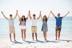 Amis heureux avec des bras augmentés à la plage Photographie stock