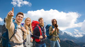 Amis heureux avec des sacs à dos augmentant au-dessus des montagnes Photos libres de droits
