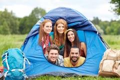 Amis heureux avec des sacs à dos dans la tente au camping Images libres de droits