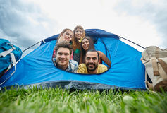 Amis heureux avec des sacs à dos dans la tente au camping Image libre de droits