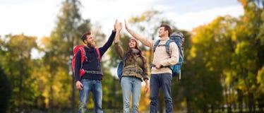 Amis heureux avec des sacs à dos faisant la haute cinq Photo stock