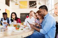 Amis heureux avec des smartphones au restaurant Photos libres de droits