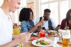 Amis heureux avec des smartphones au restaurant Images stock