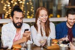 Amis heureux avec des smartphones au restaurant Photographie stock
