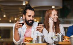 Amis heureux avec des smartphones au restaurant Images libres de droits