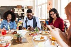 Amis heureux avec des smartphones au restaurant Photo libre de droits