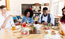 Amis heureux avec des smartphones au restaurant Photographie stock libre de droits