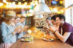 Amis heureux avec des smartphones décrivant la nourriture Photos stock