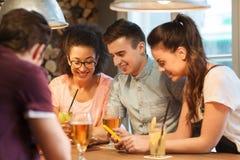 Amis heureux avec des smartphones et boissons à la barre Photos stock