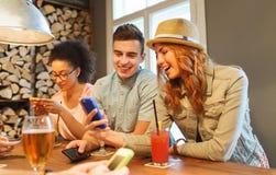 Amis heureux avec des smartphones et boissons à la barre Images stock