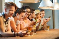 Amis heureux avec des smartphones et boissons à la barre Photo libre de droits