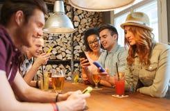 Amis heureux avec des smartphones et boissons à la barre Photographie stock