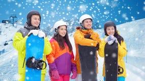 Amis heureux avec des surfs des neiges au-dessus des montagnes Photo libre de droits